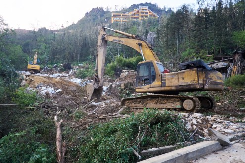 Just outside of Sa Pa town, a pair of excavators make an area of forest-land ready for a construction.
