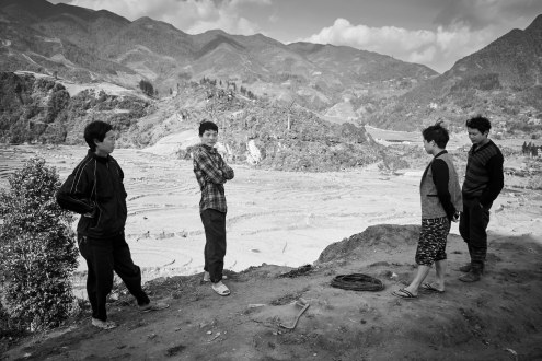 A group of men has conversation on a cliff in Ta Phin village, 10 kms away from Sa Pa town. A place where Kinh, Black Hmong and Red Yao live together.