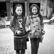 Portrait of a Hmong girl and her friend, a Red Yao girl. When the school is off, the children enjoy hanging out in the town central, some of them even sell sourvenirs.