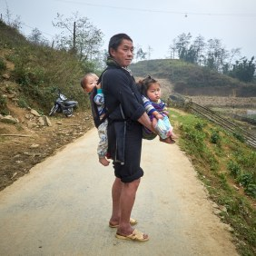 A Hmong grandfather carries his two grandchildren home from shopping.