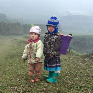 Portrait of two Hmong babies. One of them carries her laundry on her back.
