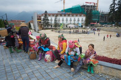 Group of Hmong street vendors take a break during lunch time. If they do not work on their farms, they go to Sa Pa town to sell souvenirs to tourists.